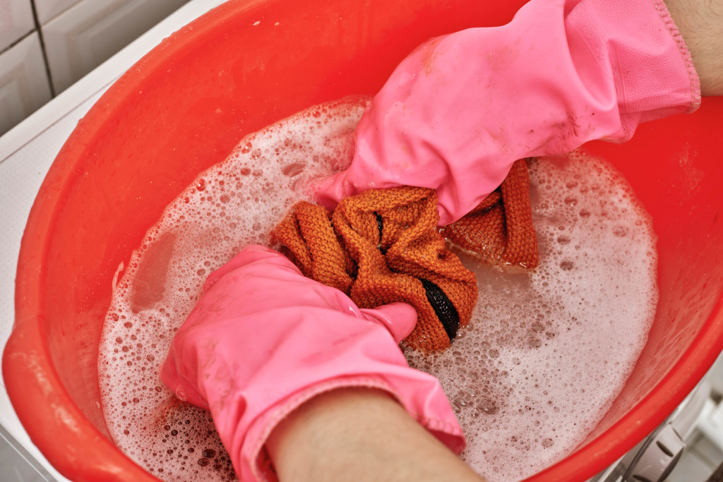 Female hands washing color clothes in washbasin