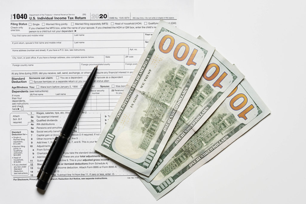 Income tax return - 1040 tax form and hundred dollar bills on white background