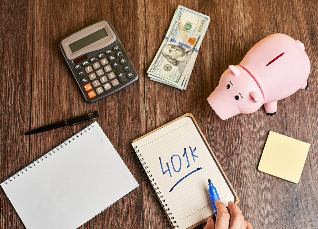 401k planning - piggy bank, calculator and notepad on the table