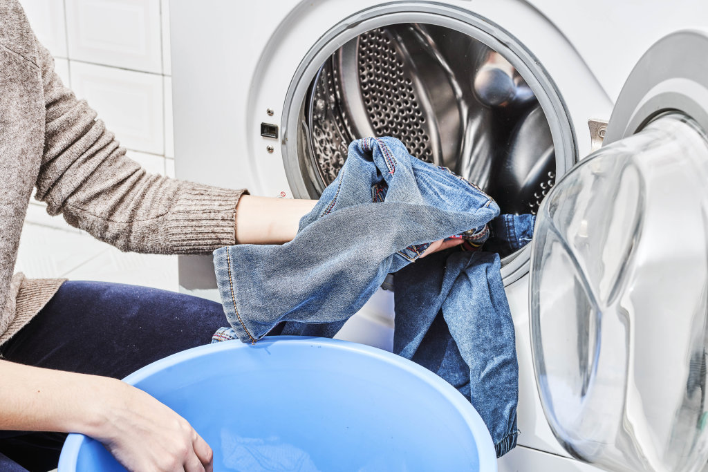 Putting jeans into the washing machine