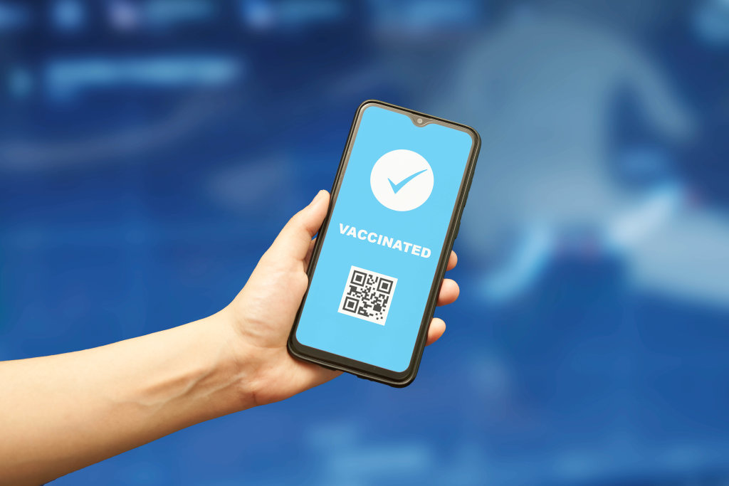 Vaccinated from COVID-19 person with digital health passport in smartphone