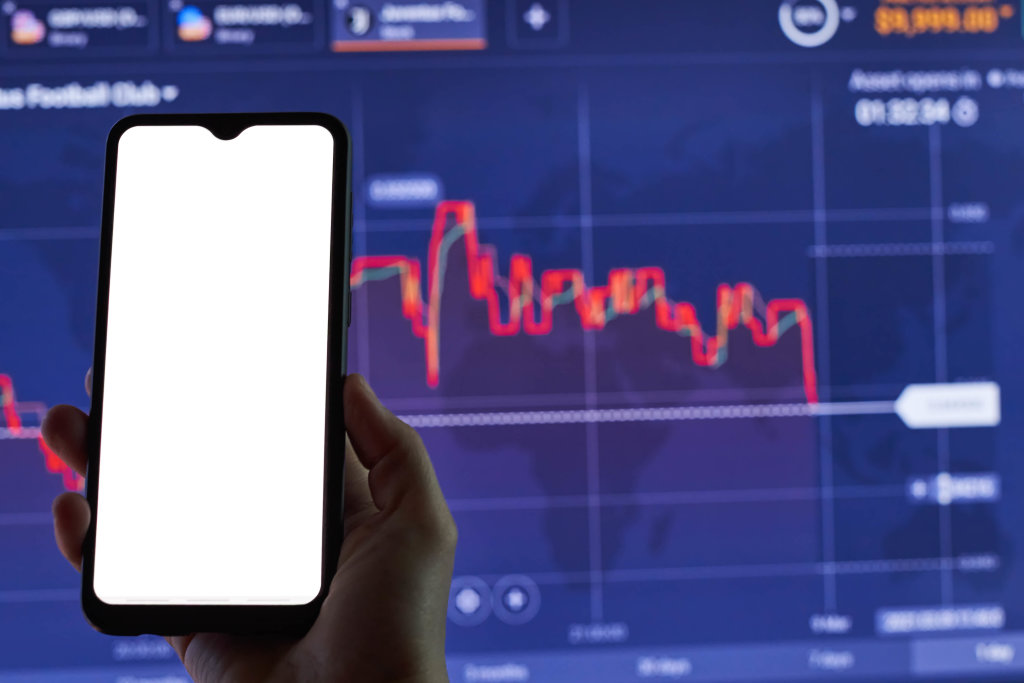 A trader holding a smartphone with an empty screen over the stock market live graphs