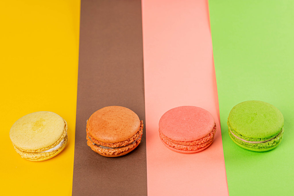 Yellow, brown, pink and green macaroons on multi-colored backgrounds