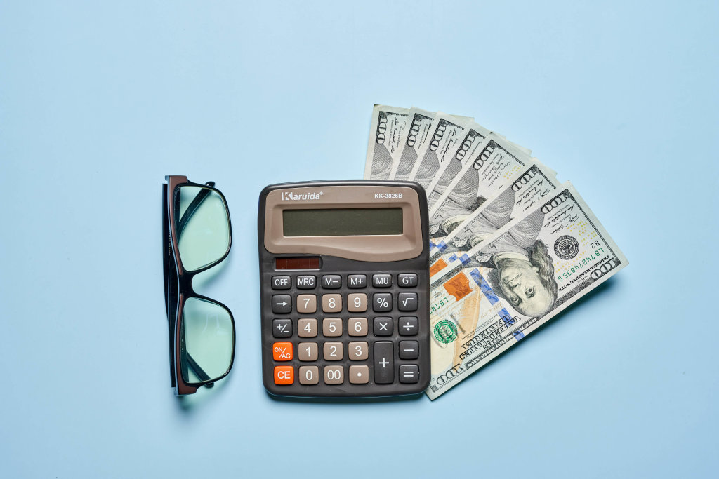 Calculator, us dollars and eyeglasses on bright blue background