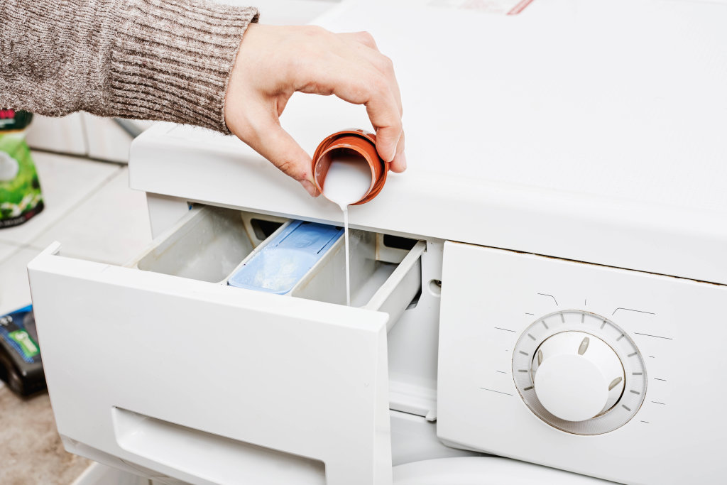 Housewife putting softner to washing machine