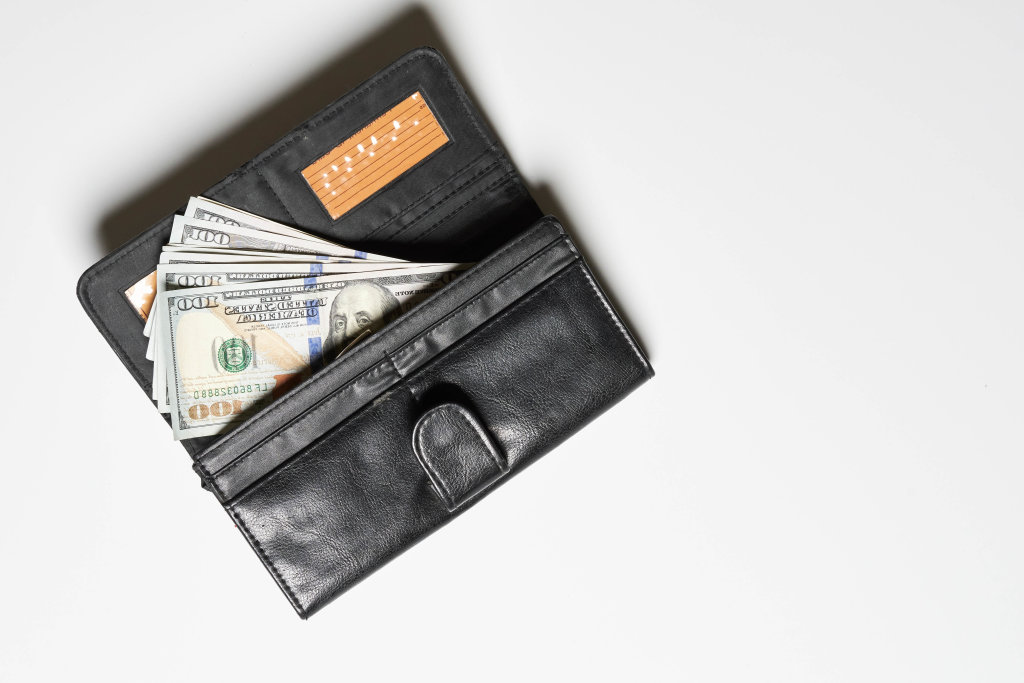 A leather wallet with a pile of us dollar banknotes