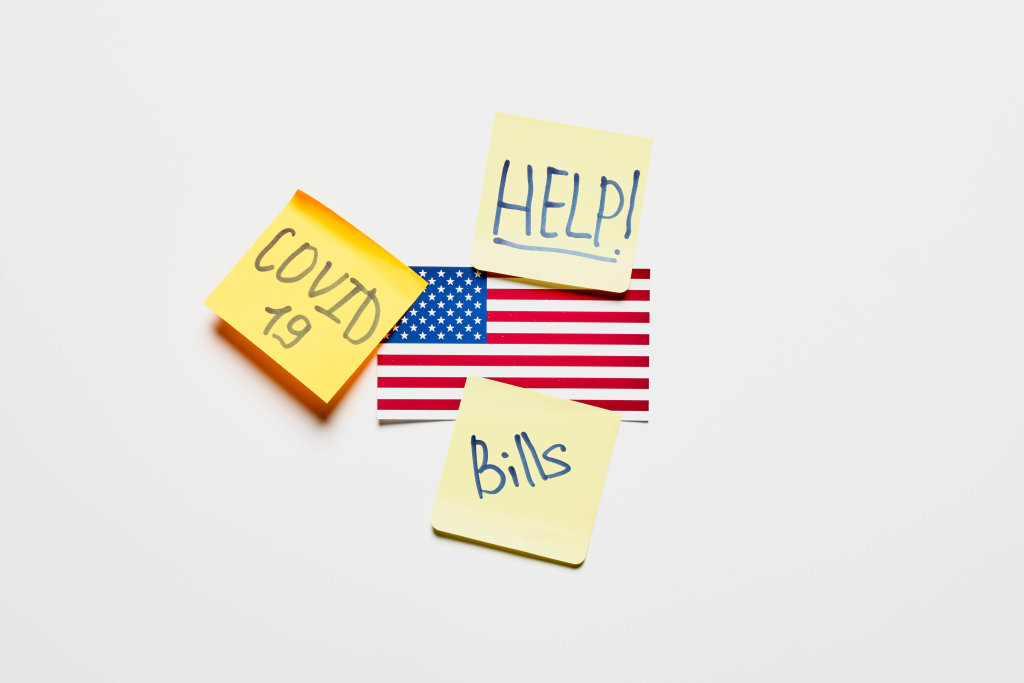 American flag and notes with Help, Covid-19 and bills texts