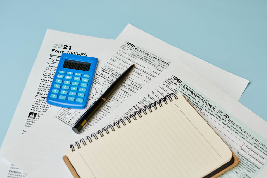 Filling 1040 tax form with calculator and pen