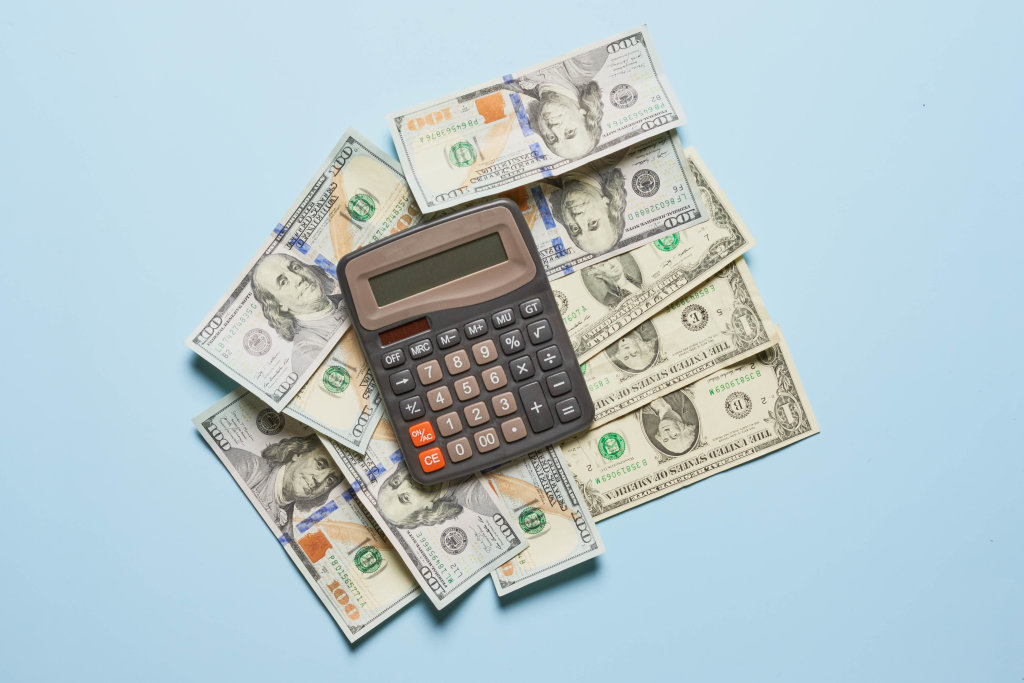 Pile of us dollar banknotes and calculator