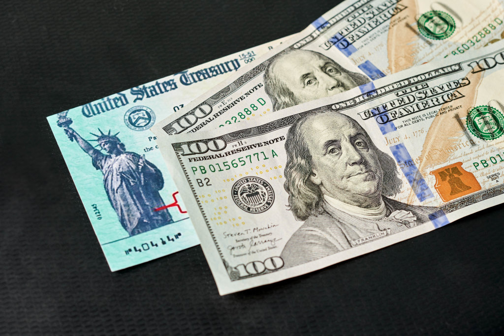 Dollar bills with US Treasury illustrative check to illustrate American Rescue Plan Act of 2021 payment