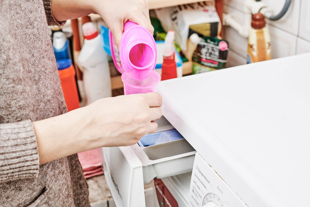 Hand pours liquid detergent into the washing machine