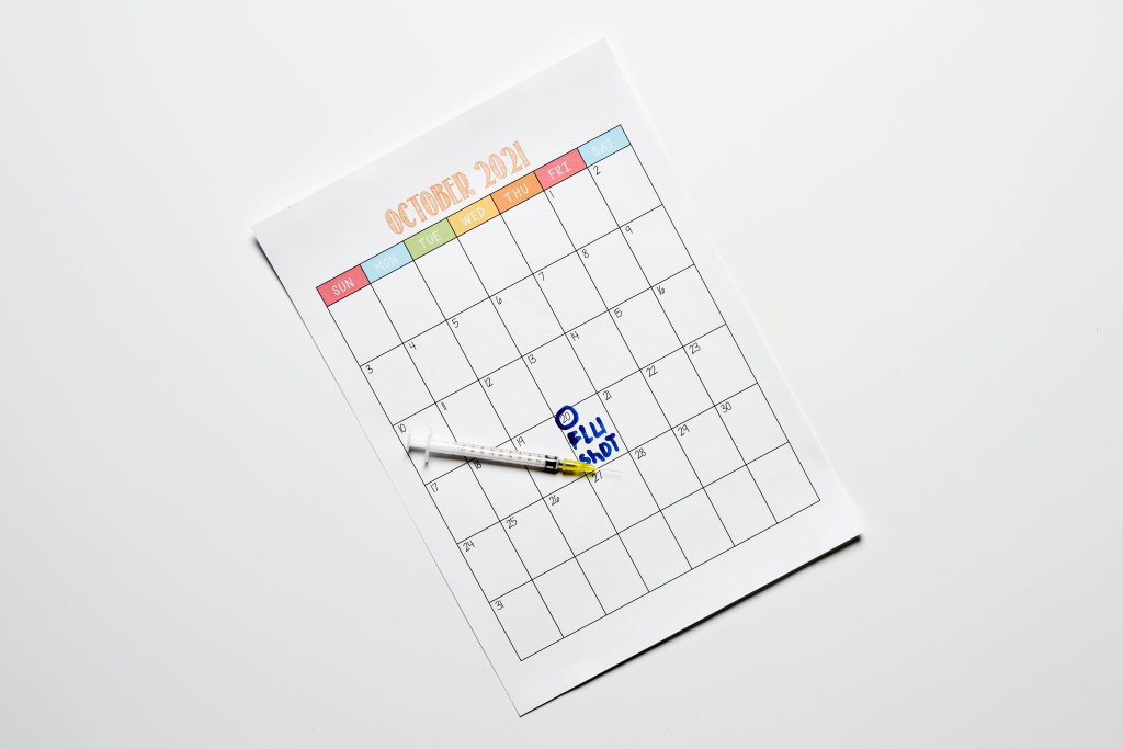 Reminder about taking flu vaccine on the calendar with a syringe