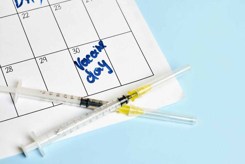 Medical syringes on calendar background