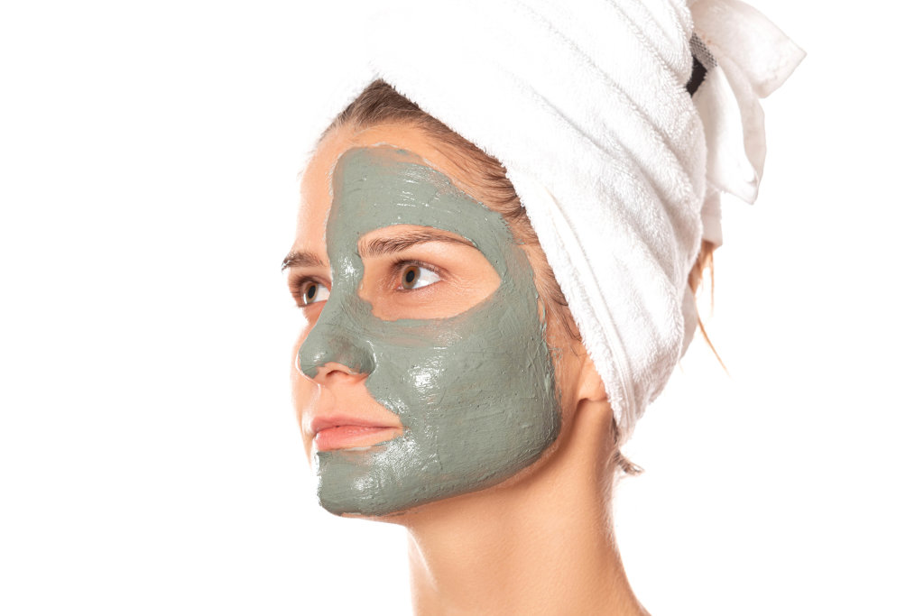 Women with a clay mask applied on their face with a white towel on their head