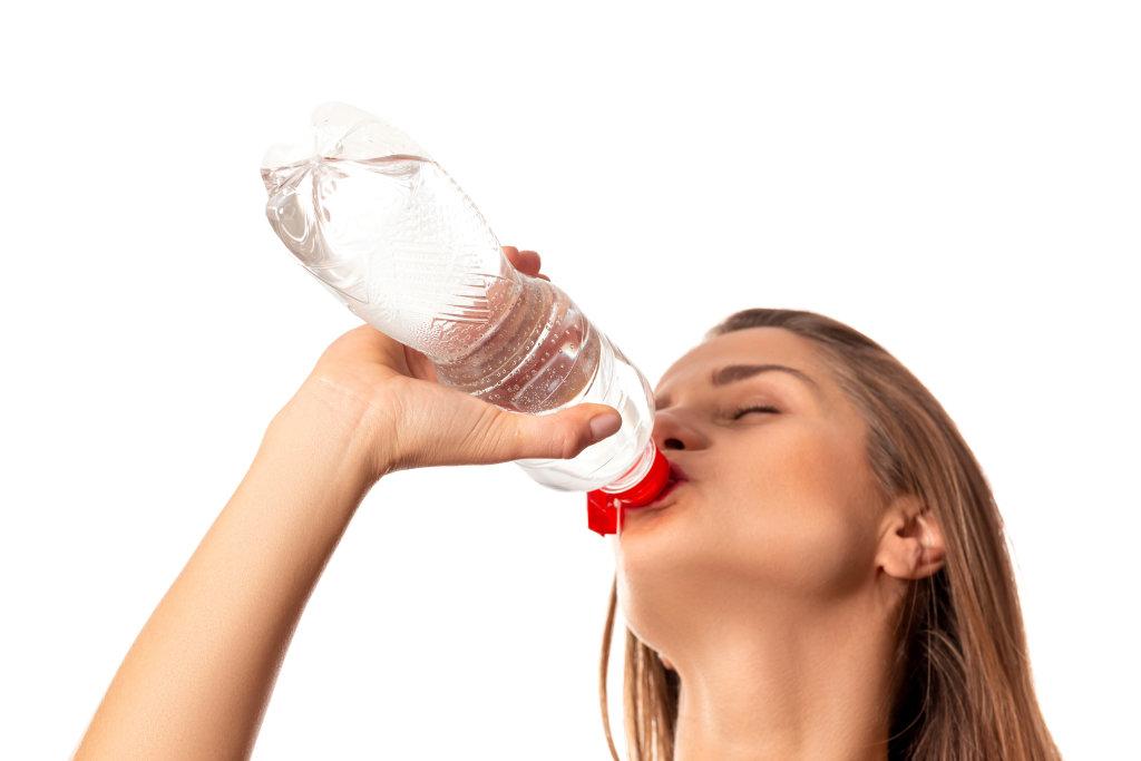 Beautiful girl drinking water from bottle