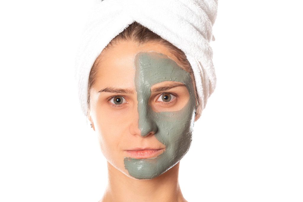 Portrait of a woman with a clay mask applied to half of her face