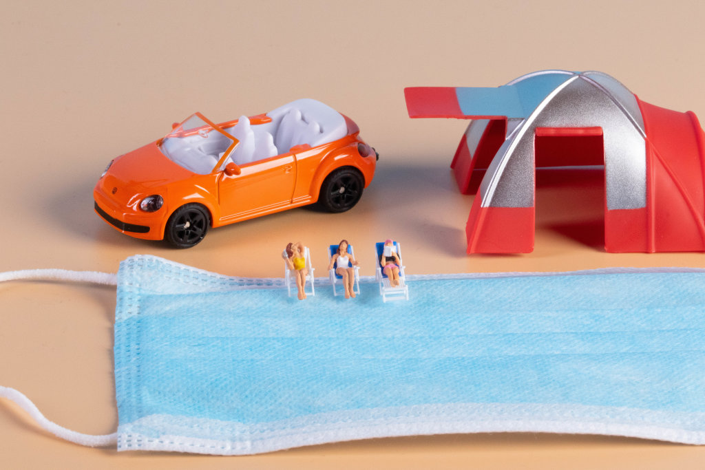 Miniature people sunbathing in deckchairs with face mask and camping tent