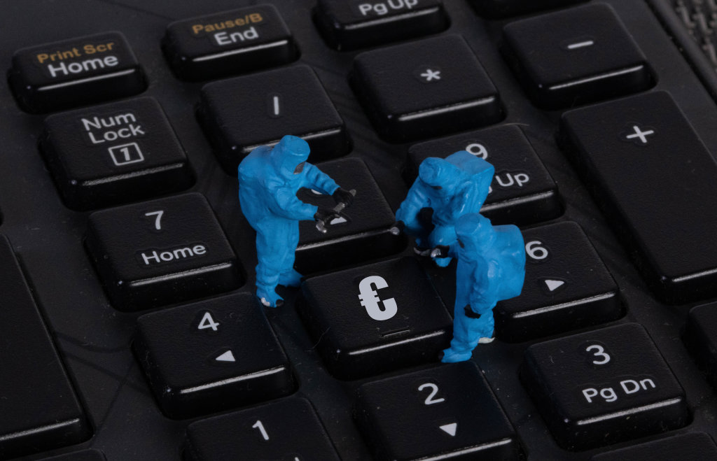 Miniature workers in protective clothes on a keyboard with Euro button