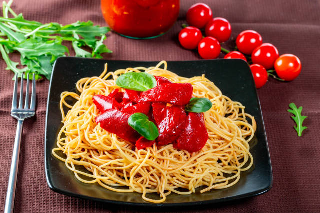 Black plate with delicious spaghetti with vegetables and fork
