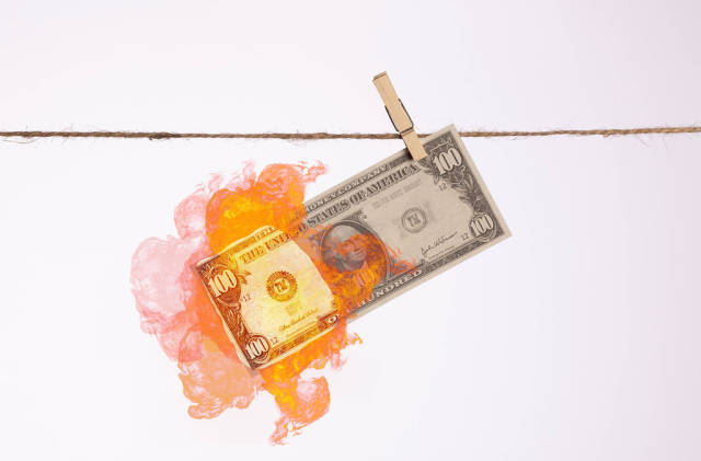 Burning dollar banknote hanging on a clothes line