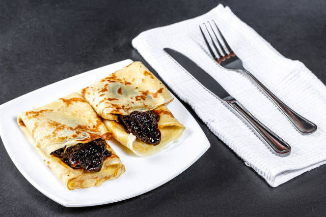 Sweet homemade pancakes with jam and Cutlery
