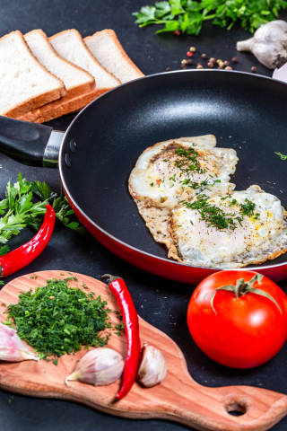 The concept of cooking Breakfast-fried chicken eggs in a frying pan with slices of bread, herbs and vegetables