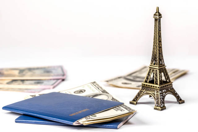 Concept of travel, vacation or leisure planning. Money, two passports and the Eiffel tower