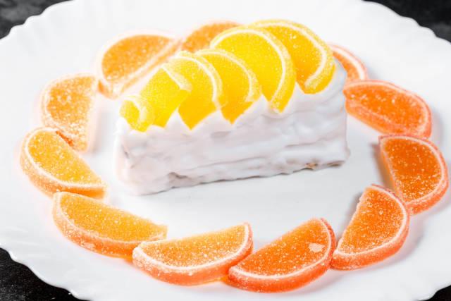 Sweet dessert with cream, orange and lemon marmalade on a white plate