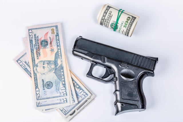 Crimes concept, with guns and dollar bills on white background