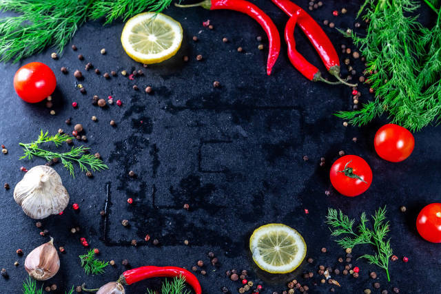 Garlic, lemon, dill and spices with cherry tomatoes on a dark background