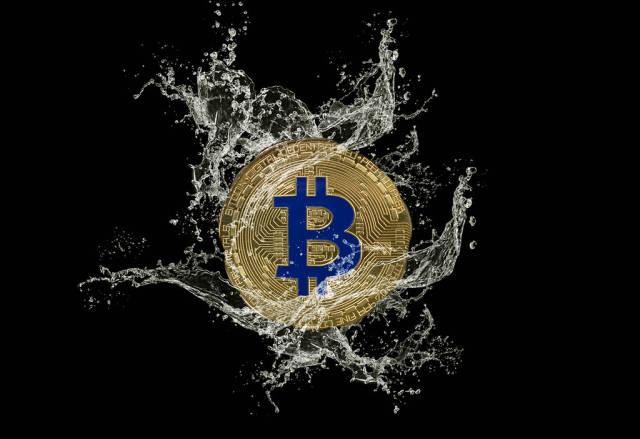 Golden Bitcoin and water splash on dark background
