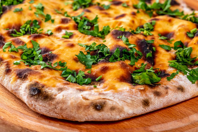 Khachapuri with cheese and herbs on wooden kitchen Board
