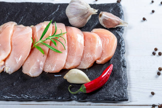 Top View Food Photo of Slices of Raw Chicken Breast, Garlic, Chili and Fresh Pepper on Black Cutting Board