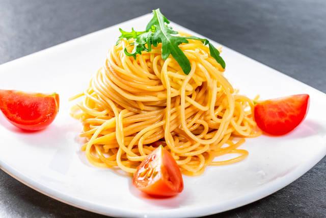Boiled spaghetti with tomato slices and arugula leaves