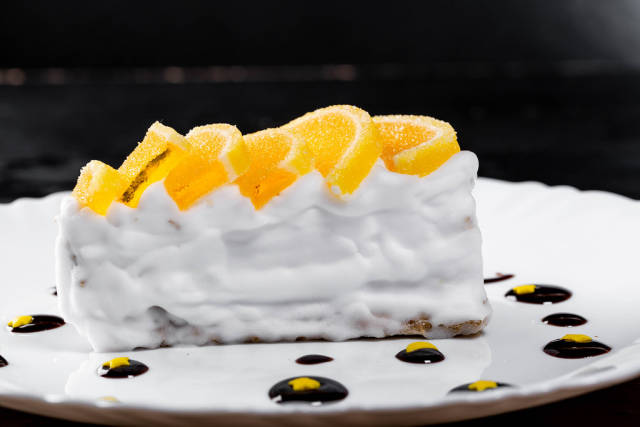 A piece of cake with Meyer lemon curd, white cream, and chocolate sauce