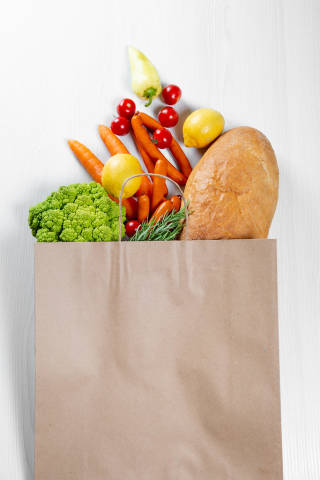 Top View Photo of Paper Bag with Fresh Vegetables and a Baguette on White Wooden Background