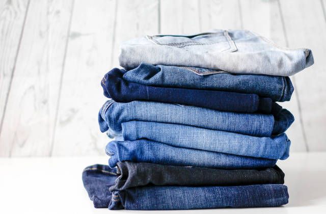 Stack of Different Colored Jeans with White Wooden Background