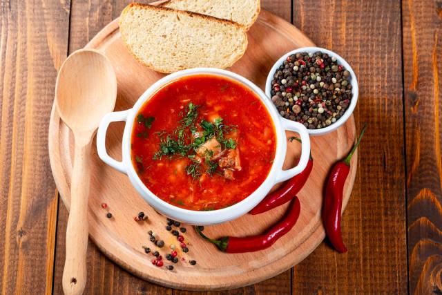 Top View Food Photo of Tomato Soup with Fresh Pepper, Chilis and Slices of Bread on Wooden Cutting Board