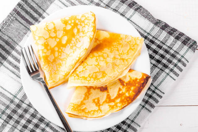 Fried pancakes on a plate with a fork and a kitchen towel
