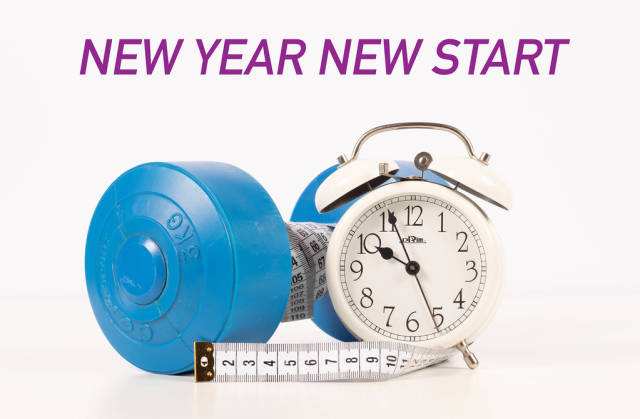 Dumbbell and alarm clock with New year new start text