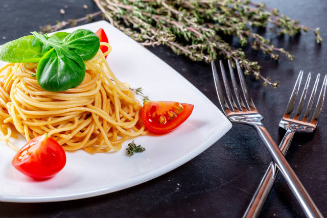 Spaghetti with forks, tomatoes and rosemary