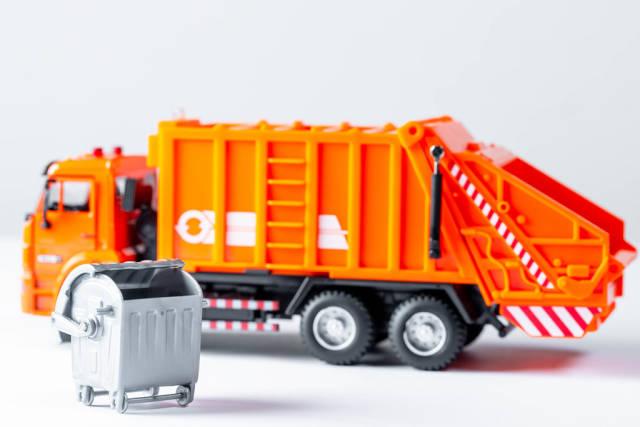 Orange garbage truck toy on a white background