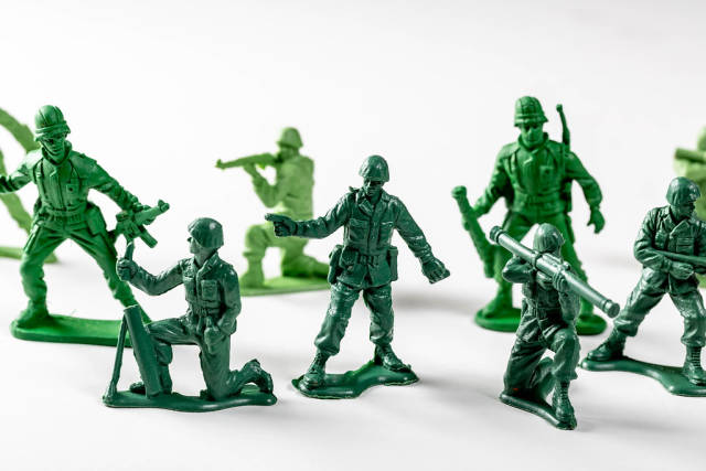 Close Up Photo of Miniature Toy Soldiers with different Guns on White Background