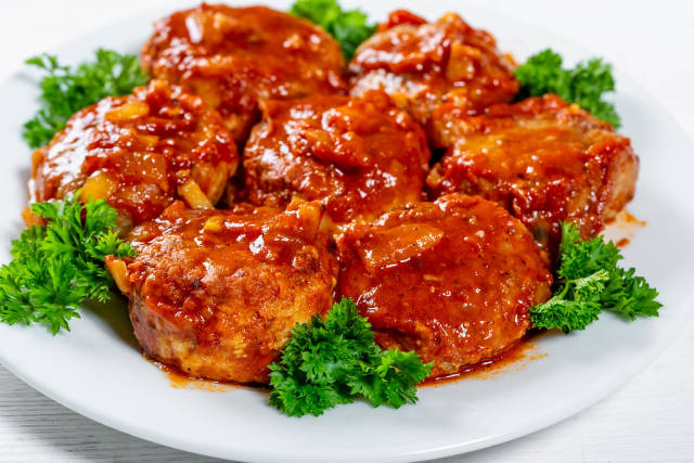 Close Up Food Photo of Meatballs with Tomato Sauce and Parsley on White Plate