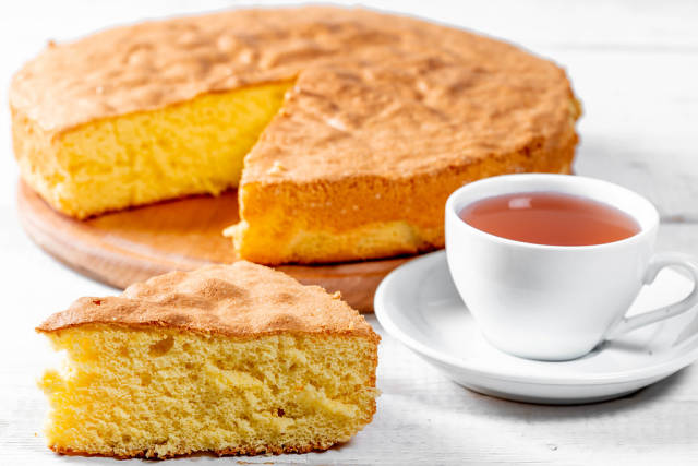 Close Up Photo of Cup of Tea next to a Piece of Cake with Sponge Cake in the Background