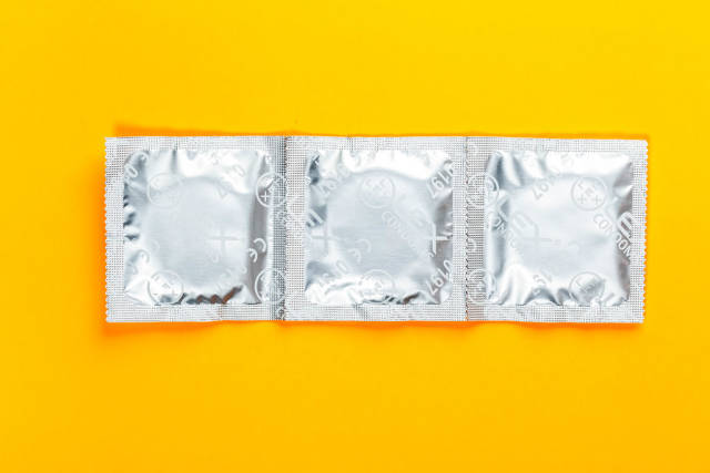 Condoms on a yellow background. Top view