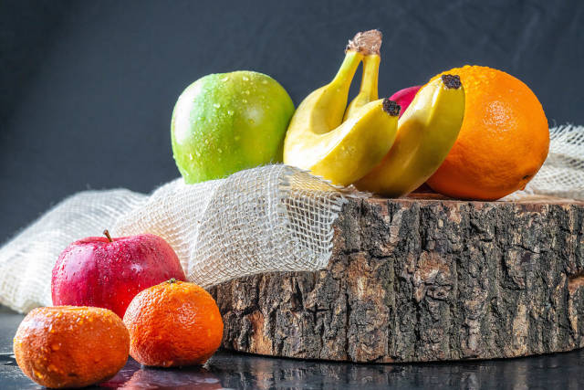 Fresh fruit with wooden stump and burlap on black table