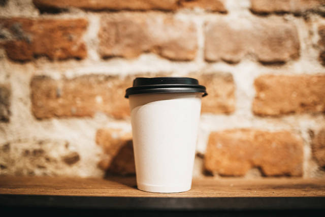 White Paper Coffee Cup with Plastic Cap in front of Brick Wall Background