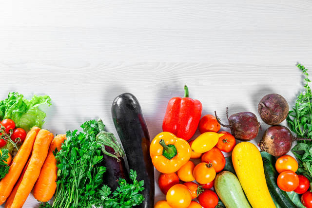 Top View Photo of Fresh Vegetables like Carrots, Bell Peppers, Cherry Tomatoes and Pumpkin on White Wooden Background