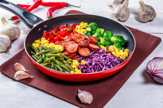 Asparagus, Brussels sprouts, corn, peppers and sausages in a frying pan
